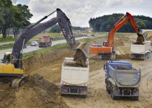 koparki lądujące ziemie na cieżarówki